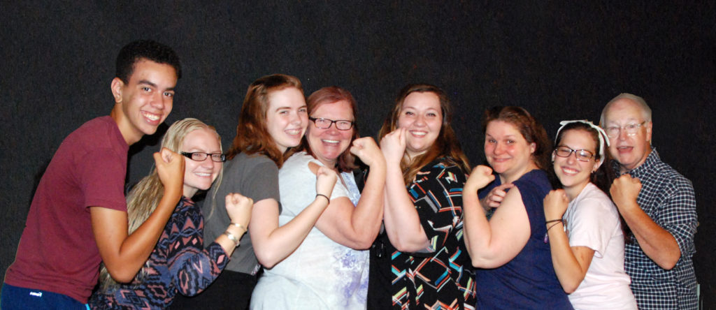 A group of actors strike the Rosie the Riveter pose