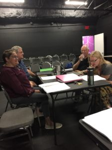 Actors and playwright sit around a table in the black box theater to read and review a new play script.