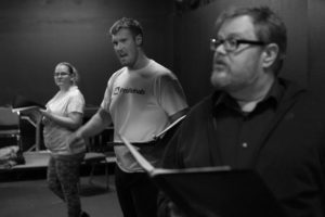 The actors playing Daisy, J.R., and Harrisson rehearse with scripts in hand.