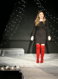 The red boots on Bella Allison take center stage - she's performing a song from Kinky Boots at the 2019 Season Announcement Cabaret. Sparkling lights are the backdrop
