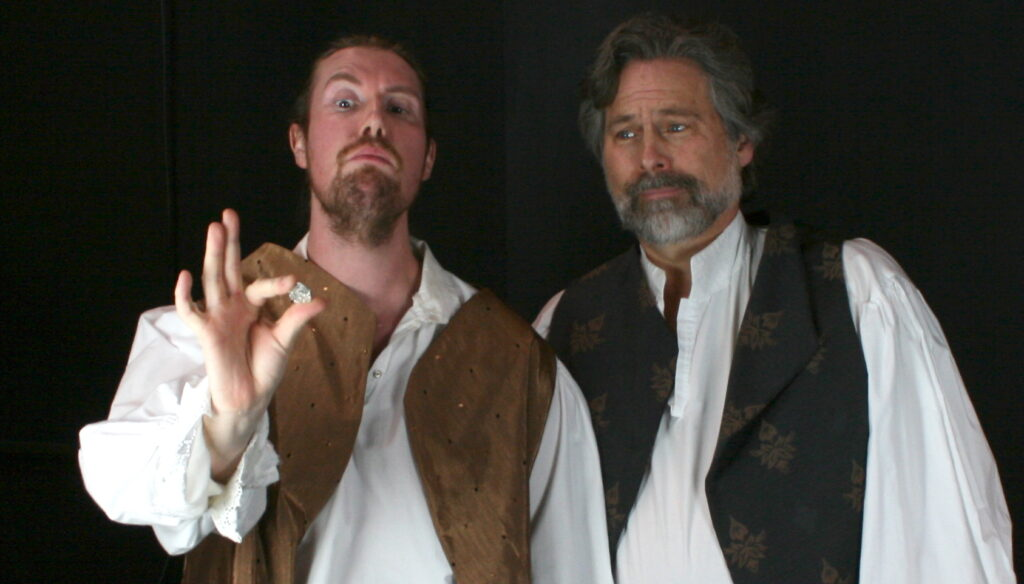 Rosencrantz holds up a coin to inspect with Guildenstern.