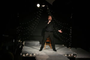 Renny holds a microphone to his mouth and stands in the spotlight for his Cabaret performance.