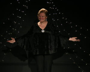 "Amber stands on the stage at the Cabaret, dressed in all black, performing ""I'm Still Here"""